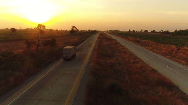 aerial view truck driving at sunset - horizon over land stock videos & royalty-free footage