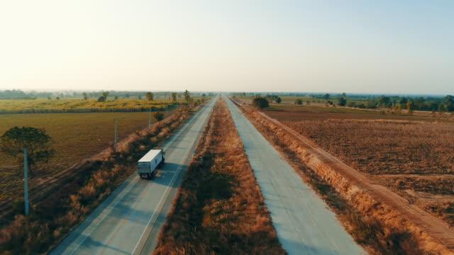 vídeos y material grabado en eventos de stock de camión de visión aérea conduciendo al atardecer - plano descripción física