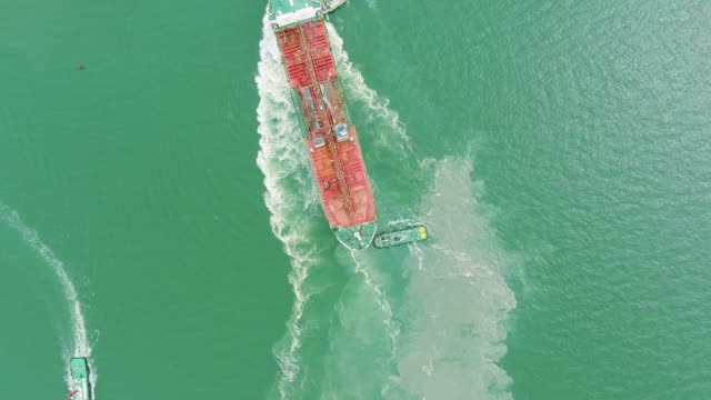 aerial view; tugboat towing the empty cargo containers ship leave shipyard after maintenance service. - cargo ship stock videos & royalty-free footage