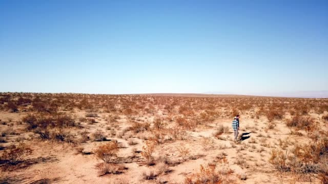 vidéos et rushes de aerial view: two men walking & talking in desert landscape during the day - ciel sans nuage