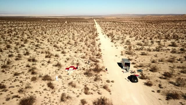 aerial view: two vehicles parked on dirt track in desert scrubland with two men - terra brulla video stock e b–roll