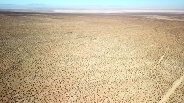 aerial view: vast, flat, desert landscape with distant mountains & blue sky - josuabaum stock-videos und b-roll-filmmaterial