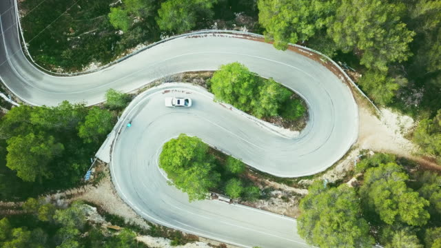 aerial view video of a two lane winding road in a forest with a cyclist and a car - winding road stock videos & royalty-free footage