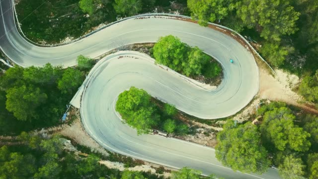 Aerial view video of a two lane winding road in a forest with a cyclist