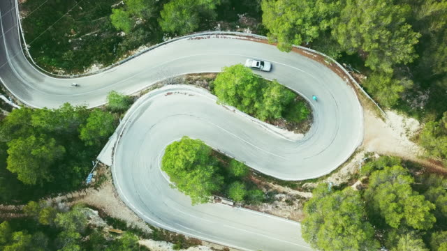 aerial view video of a two lane winding road in a forest with cyclists and a car - winding road stock videos & royalty-free footage