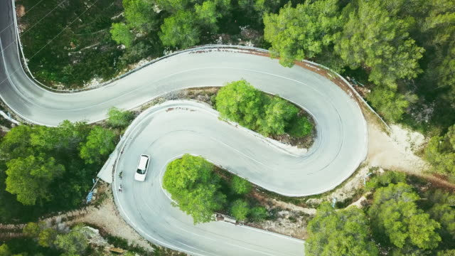 Aerial view video of a two lane winding road in a forest with cyclists and a car