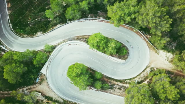vídeos de stock e filmes b-roll de aerial view video of a two lane winding road in a forest with two cyclists - alicante