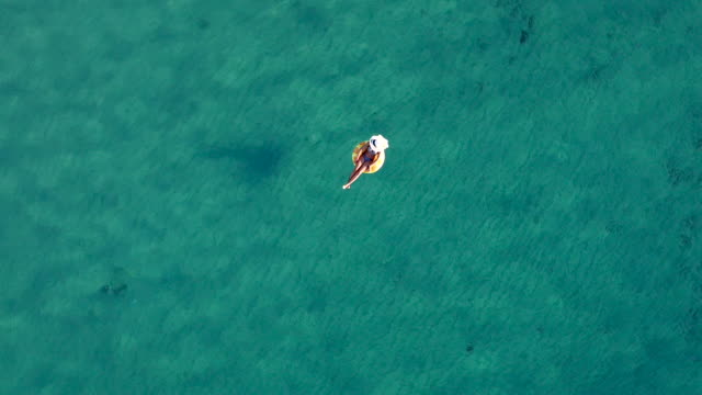 luftbild video von einer frau entspannen im meer auf aufblasbaren ring - sunbathing stock-videos und b-roll-filmmaterial