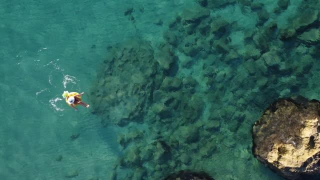 luftbild video von einer frau entspannen im meer auf aufblasbaren ring - einzelne frau über 30 stock-videos und b-roll-filmmaterial