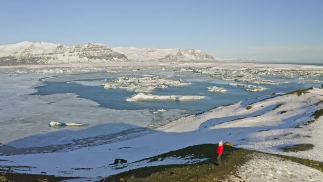aerial view video of mature woman visiting jokulsarlon lagoon, iceland - lagoon stock videos and b-roll footage
