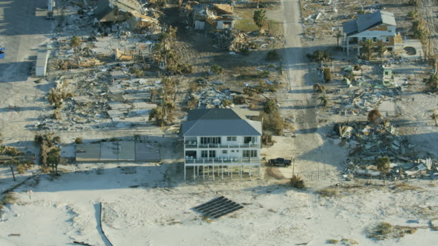 aerial view waterfront homes destroyed by hurricane michael - 防水シート点の映像素材/bロール