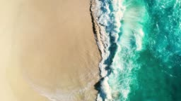 Aerial view waves break on white sand beach. Sea waves on the beautiful beach.