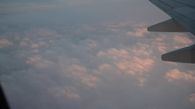 aerial view while flying at sunset of airplane over orange-red coloured clouds. - high up stock videos & royalty-free footage