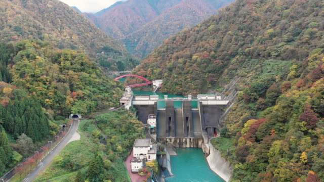 aerial view with dolly of unazuki dam in autumn season, toyama, japan. - toyama prefecture stock videos and b-roll footage