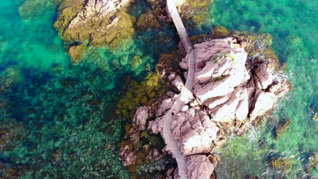 Aerial view with drone flying over a nice path between rocks in the Costa Brava shoreline.