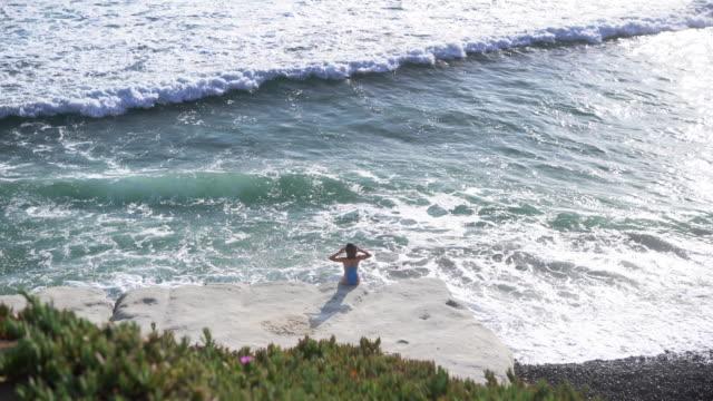 vídeos y material grabado en eventos de stock de ws rv aerial view, woman looking out to sea. - traje de baño de una pieza