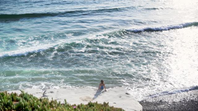 vídeos y material grabado en eventos de stock de ws rv aerial view, woman looking out to sea - traje de baño de una pieza