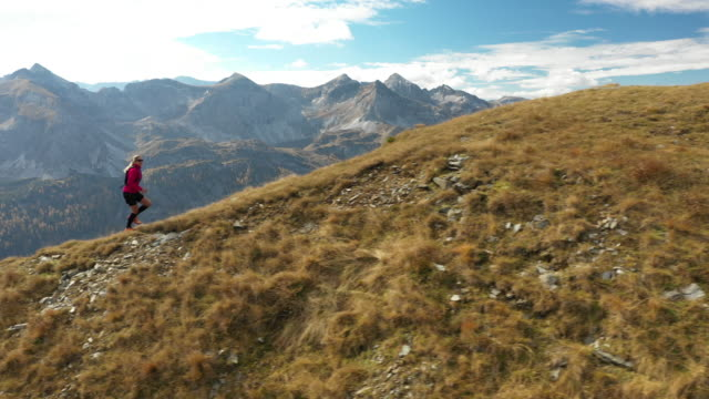 4K aerial view woman trail running on ridge in mountains