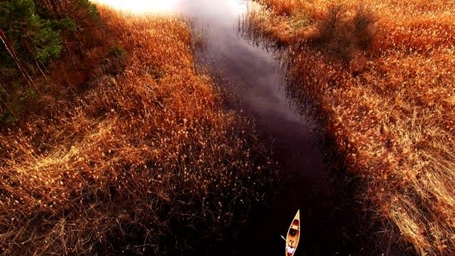 aerial view: wooden canoe on dark lake in spring - moor stock videos & royalty-free footage