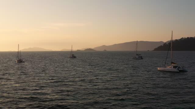 luftaufnahme yacht verankert schwimmend auf dem ozean in sonnenuntergang sendezeit - anchored stock-videos und b-roll-filmmaterial