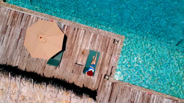 aerial view Young woman at swimming in ocean front villa pool