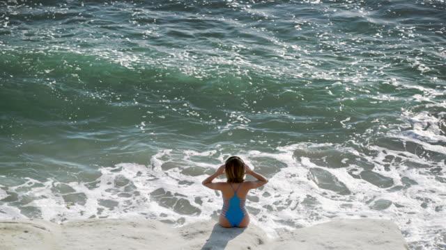 vídeos y material grabado en eventos de stock de ws rv aerial view, young woman looking at the sea - traje de baño de una pieza
