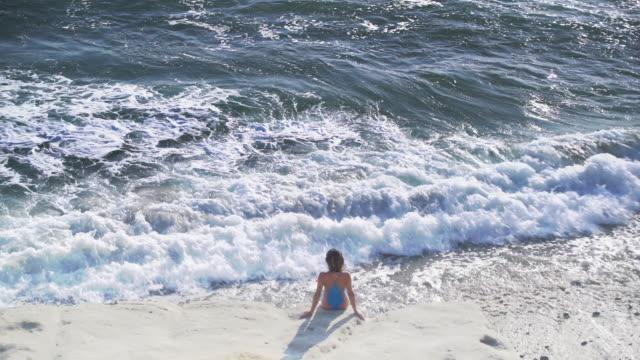 vídeos y material grabado en eventos de stock de ws rv aerial view, young woman looking at the water - traje de baño de una pieza