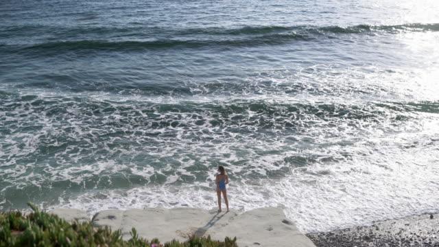 vídeos y material grabado en eventos de stock de ws aerial view, young woman watching the waves - traje de baño de una pieza