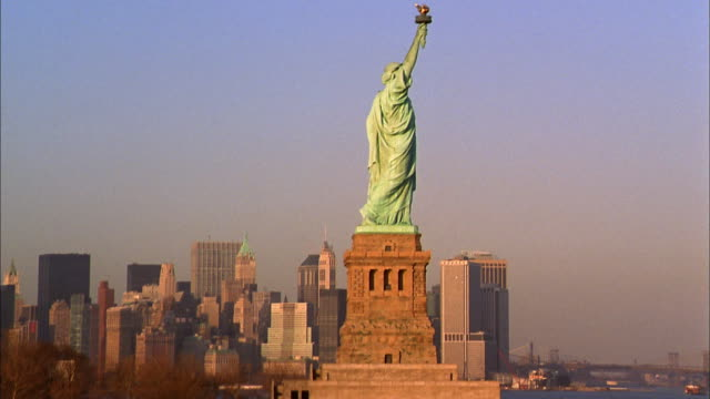 aerial view zoom in statue of liberty w/manhattan skyline in background - statue of liberty new york city bildbanksvideor och videomaterial från bakom kulisserna
