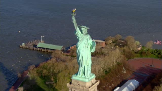 vídeos de stock, filmes e b-roll de aerial view zoom out circling statue of liberty in new york harbor / new york, new york - estátua