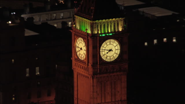 Aerial view zoom out from Big Ben and Houses of Parliament to Thames at night / London, England