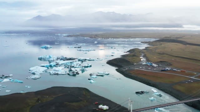 4k aerial view zooming footage icebergs in jokulsarlon lagoon with dramatic clouds - jokulsarlon stock-videos und b-roll-filmmaterial