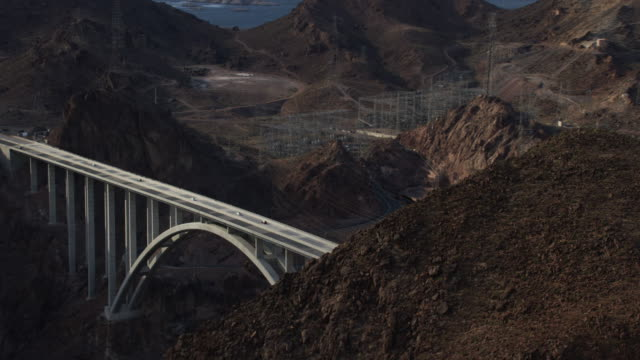 aerial view zooming in and out of the mike o'callaghan–pat tillman memorial bridge and hoover dam - ネバダ州クラーク郡点の映像素材/bロール
