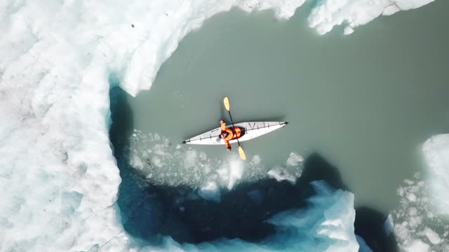 vídeos de stock e filmes b-roll de aerial view zooming out from kayaker near iceberg - kayaking