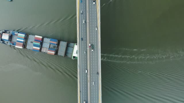 aerial view/a large cargo ship was sailing in a river under a bridge with car traffic. - southeast asia stock videos & royalty-free footage