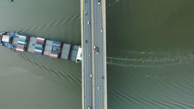 aerial view/a large cargo ship was sailing in a river under a bridge with car traffic. - sydostasien bildbanksvideor och videomaterial från bakom kulisserna