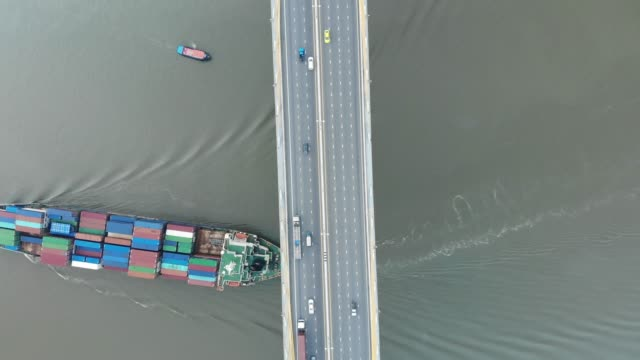 aerial view/a large cargo ship was sailing in a river under a bridge with car traffic. - on top of stock videos & royalty-free footage