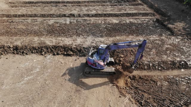 aerial view/backhoe is digging the soil for farming - bagger stock-videos und b-roll-filmmaterial