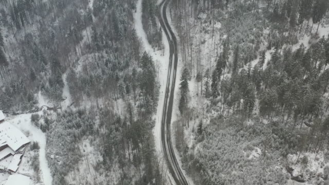 aerial views above a car that drives up a curvy wintery road in heavy snowfall - bavarian alps stock videos & royalty-free footage