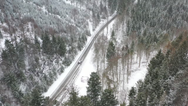 aerial views following a car on a wintery road through an alpine forest in heavy snowfall - european alps stock videos & royalty-free footage