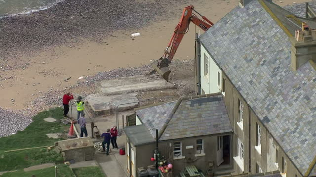 aerial views houses at Birling Gap beside National Trust cafe mechanical digger clearing ground near houses very close to cliff edge due to winter...