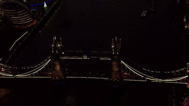 london aerial views london bridge over ther thames lit up at night - tower bridge stock videos & royalty-free footage