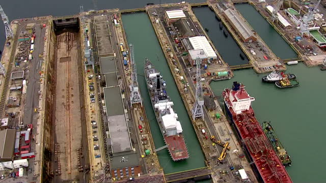 aerial views of a dry dock and flooded dry docks at portsmouth naval shipyards with various ships under construction or undergoing maintenance in... - costruttore navale video stock e b–roll