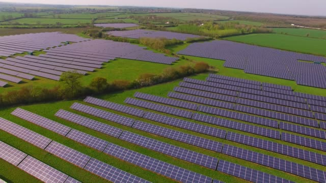 aerial views of a large solar energy generation farm in northamptonshire england uk - northamptonshire stock videos & royalty-free footage
