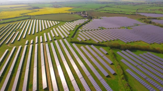 aerial views of a large solar energy generation farm in northamptonshire england uk - renewable energy stock videos & royalty-free footage