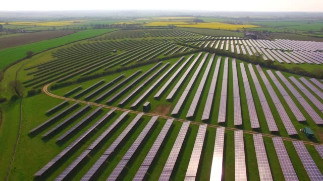 aerial views of a large solar energy generation farm in northamptonshire england uk - solar panel stock videos & royalty-free footage