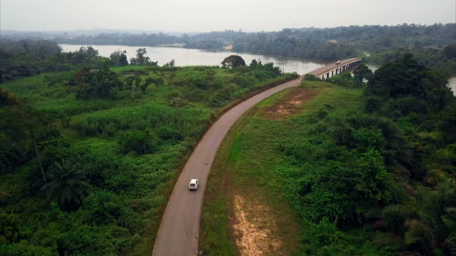 """aerial views of a rural road through forest, gabon - """"bbc universal"""" stock videos & royalty-free footage"""