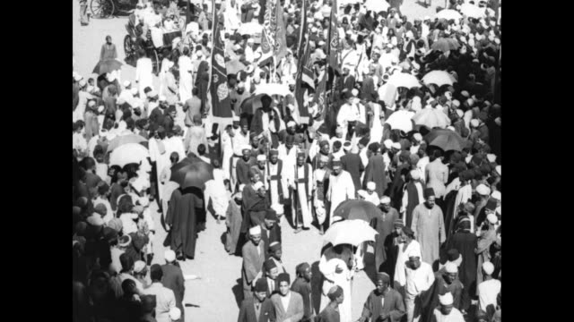 aerial views of a throng of people crowded around participants in a crowded religious procession; many people hold umbrellas to shield themselves... - headdress stock videos & royalty-free footage