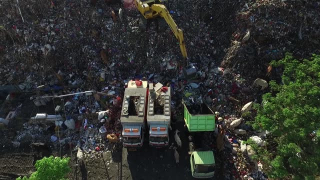 vidéos et rushes de aerial views of a truck unloading garbage while a man operates an excavator as waste pickers sift through garbage and cows scavange in the trash at a... - se nourrir des restes