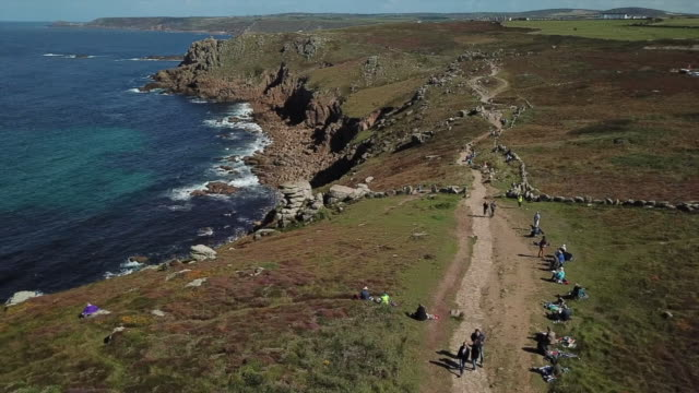 vidéos et rushes de aerial views of around a thousand artists gathered at land's end to raise awareness about coastal erosion - érodé